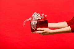 Übergeben Sie das Mädchen, das eine Geschenkbox auf rotem Hintergrund hält Lizenzfreies Stockbild