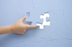 Übergeben Sie das Montieren eines Teils eines Puzzlespiels Stockfotos