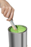 Übergeben Sie das Rühren der grünen Farbe mit dem hölzernen Stock, der auf weißem Hintergrund lokalisiert wird Lizenzfreies Stockfoto
