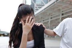 Übergeben Sie das ` s des Kollegen deprimierte traurige Asiatin mit den Händen auf dem Gesichtsschreien tröstend Stockfoto