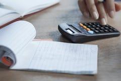 Übergeben Sie das Schreiben auf einem Taschenrechner während der Steuerjahreszeit mit einem Notizbuch im Vordergrund Lizenzfreie Stockfotos