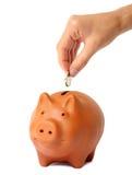 Übergeben Sie das Setzen der Münze in die piggy Querneigung Lizenzfreies Stockbild