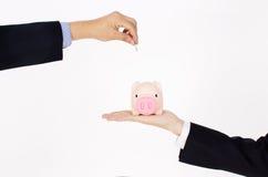 Übergeben Sie das Setzen der Münze in eine piggy Querneigung Lizenzfreie Stockfotografie