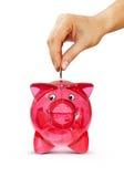 Übergeben Sie das Setzen der Münze in piggy Querneigung Lizenzfreie Stockbilder