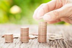 Übergeben Sie das Setzen der Münze zum Geld mit Sonnenlicht, Geschäftsideen Lizenzfreie Stockbilder