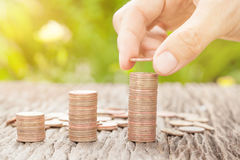 Übergeben Sie das Setzen der Münze zum Geld mit Sonnenlicht, Geschäftsideen Stockfotografie