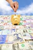 Übergeben Sie das Setzen einer Münze in ein Sparschwein mit unterschiedlicher Währung Lizenzfreies Stockbild