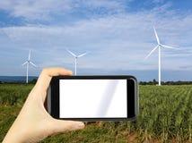 übergeben Sie das Shoting durch intelligentes Telefon mit Hintergrundwindkraftanlagen windmi Lizenzfreie Stockfotos