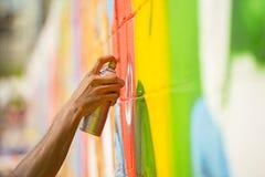 Übergeben Sie das Sprühen, zum der Straßenkunst auf Wand zu malen Stockbild