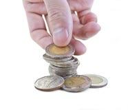 Hand, welche die thailändischen Münzen lokalisiert auf Weiß stapelt Stockfotografie