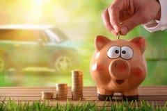 Übergeben Sie das Stecken des Geldes in Sparschwein, um ein Auto zu kaufen Lizenzfreies Stockbild