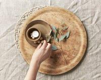Übergeben Sie das Vereinbaren einer Kerze und des einfachen Dekors mit Blättern Lizenzfreie Stockfotos