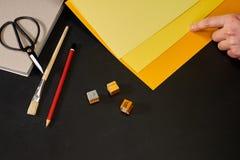 Übergeben Sie das Wählen des gelben Schattens mit Kreativitätswerkzeugen auf Schwarzem Stockfotografie