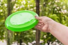 Übergeben Sie das Werfen einer Frisbeediskette im Park an einem Sommertag lizenzfreies stockfoto
