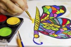 Übergeben Sie das Zeichnen eines bunten Schmetterlinges mit einer Bürste und funkeln Sie Stockfoto