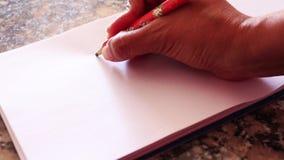 Übergeben Sie das Zeichnen eines Herzens auf einem einfachen Weißbuch volles HD 1920x1080 stock footage
