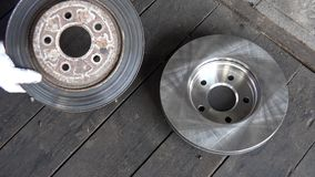 Übergeben Sie das Zeigen der schlechten getragenen Bremsscheibe mit Kontrast zum Neuen auf Bretterboden stock footage