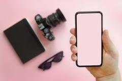 Übergeben Sie das Zeigen des stilvollen schwarzen Telefons mit leerem Schirm, Sonnenbrille, c Lizenzfreie Stockfotos