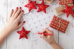 Übergeben Sie das Zeigen am 25. Dezember in einen Kalender, der durch Weihnachtsverzierungen umgeben wird Lizenzfreies Stockfoto