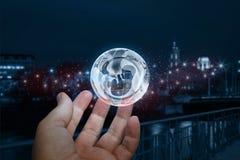 Übergeben Sie das Zeigen von Erde mit einem menschlichen Embryo auf unscharfem Hintergrund Lizenzfreies Stockfoto