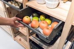 Übergeben Sie das Ziehen des Metallküchenfaches, das mit gefälschten Äpfeln für Di gefüllt wird stockfoto