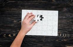 Übergeben Sie den Abschluss von wthite Puzzlespiel mit dem letzten Stück Stockfotografie