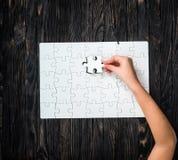 Übergeben Sie den Abschluss von wthite Puzzlespiel mit dem letzten Stück Stockbild