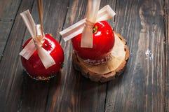 Übergeben Sie den eingetauchten Karamellapfel, der mit multi Farbe bedeckt wird, besprüht Stockfotos