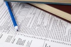 übergeben Sie den Holdingbleistift, platziert auf grafische Diagramme 1040 Steuerformular und ein blauer Stift Lizenzfreie Stockbilder