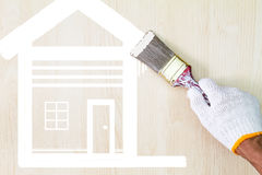 Übergeben Sie den tragenden weißen Handschuh, der alten Schmutzmalerpinsel hält und weißes Haussymbol auf hölzerner Wand malt Stockbilder
