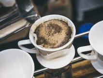 Übergeben Sie den Tropfenfänger-Kaffee, der Heißwasser auf Kaffeesatz ausläuft stockbild