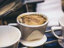 Übergeben Sie den Tropfenfänger-Kaffee, der Heißwasser auf Kaffeesatz ausläuft stockfotos