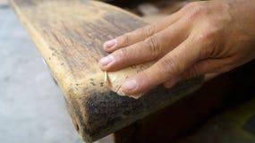 Übergeben Sie Detail unter Verwendung des Sandpapiers, um einen alten Sofaarm zu säubern Stockbild