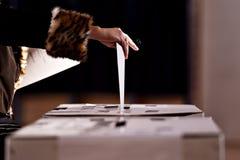 Übergeben Sie die Abgabe einer Abstimmung in die Wahlurne Lizenzfreie Stockfotografie