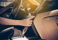Übergeben Sie die Frau, die AutoKlimaanlage einschaltet, Finger einschalten Luftknopf, Knopf auf Armaturenbrett in der Autoplatte lizenzfreie stockfotografie