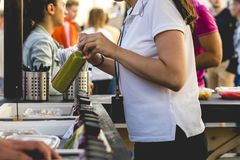 Übergeben Sie die Frau, welche die Flasche des frischen Safts Speicher im im Freien an einem Sommertag verkauft stockfotografie