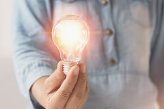 übergeben Sie die Geschäftsfrau, die Glühlampe, Innovation und inspiratio hält lizenzfreie stockfotos