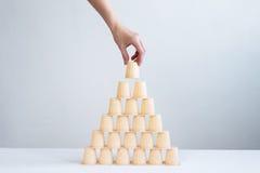 Übergeben Sie die Herstellung einer Pyramide von wenigen Plastikgläsern Lizenzfreies Stockbild