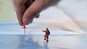 übergeben Sie die Platzierung eines roten Stiftes mit Reisendminiaturminizahl mit Stockfoto