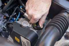 Übergeben Sie die Prüfung der Ölkappe eines Automotors Stockfotografie