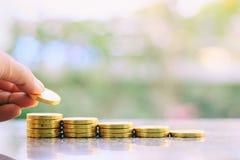 Übergeben Sie die Rettung einer Münze auf dem Stapel des Geldes Stockfotografie