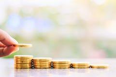 Übergeben Sie die Rettung einer Münze auf dem Stapel des Geldes gegen unscharfes natürliches Stockbild