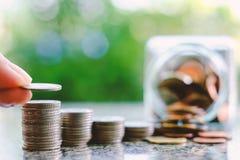 Übergeben Sie die Rettung einer Münze auf dem Stapel des Geldes verwischte an das Glas-ja Lizenzfreie Stockfotos