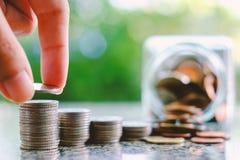 Übergeben Sie die Rettung einer Münze auf dem Stapel des Geldes verwischte an das Glas-ja Lizenzfreies Stockfoto
