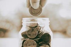 Übergeben Sie die Rettung einer Münze in das Glasgefäß auf unscharfem grünem natürlichem b Lizenzfreie Stockbilder