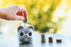 Übergeben Sie die Rettung einer Münze in Sparschwein Stockfoto