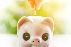 Übergeben Sie die Rettung einer Münze in Sparschwein Stockbild