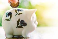 Übergeben Sie die Rettung einer Münze in Sparschwein Stockbilder