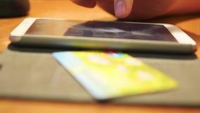 Übergeben Sie eine Überweisung des Geldes mit Kreditkarte unter Verwendung eines Smartphone stock footage