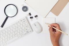 Übergeben Sie Gebrauchsbleistiftschreiben auf Weißbuchanmerkungs- und -geschäftsgegenständen Stockbild